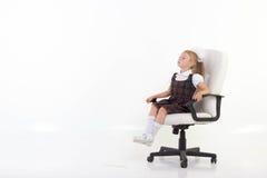A menina senta-se orgulhosamente em uma cadeira Foto de Stock