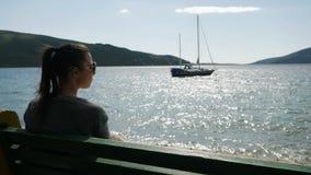 A menina senta-se pelo mar em um banco vídeos de arquivo