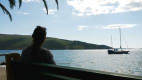A menina senta-se pelo mar em um banco video estoque