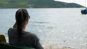 A menina senta-se pelo mar em um banco filme