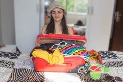 A menina senta-se perto da mala de viagem aberta Preparar-se para viajar Imagens de Stock