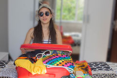 A menina senta-se perto da mala de viagem Menina ao lado da mala de viagem enchida em demasia Preparar-se para viajar Bom dia par Fotos de Stock