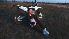A menina senta-se perto de uma motocicleta e aprecia-se o por do sol vídeos de arquivo