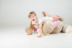 Menina sentada com brinquedo peluches e sorriso Fotos de Stock Royalty Free