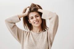 A menina sente como precisa de visitar o cabeleireiro Retrato da fêmea atrativa despreocupada com cabelo de levantamento do sorri Imagens de Stock Royalty Free