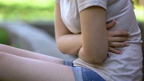 A menina sente a dor de estômago fora, problemas com sistema digestivo, grampos dolorosos imagens de stock royalty free