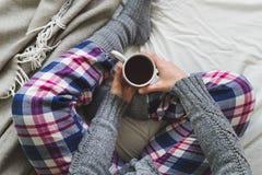 A menina sentou-se na cama em pyjamas acolhedores que bebe um copo do chá fotografia de stock royalty free