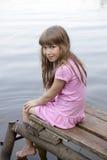 Menina sete anos de assento velho na ponte velha Imagens de Stock Royalty Free