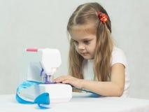 Menina que sewing na máquina de costura Fotos de Stock Royalty Free