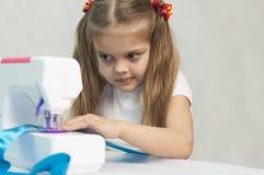 Menina que sewing na máquina de costura Fotos de Stock