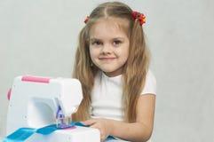 Menina que sewing na máquina de costura Fotografia de Stock Royalty Free