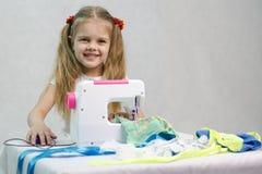 Menina que sewing na máquina de costura Fotografia de Stock
