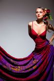 Menina sexual no vestido vermelho com as flores em seu cabelo fotografia de stock royalty free