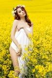 Menina 'sexy' atrativa nova em um dia ensolarado do campo de florescência da violação com as flores no cabelo vermelho Fotografia de Stock Royalty Free