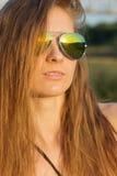 Menina 'sexy' bonita com cabelo longo com os óculos de sol vestindo bronzeados da pele na praia do dia morno ensolarado Fotografia de Stock