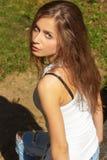 Menina 'sexy' bonita com cabelo longo em um t-shirt branco e nas calças de brim que sentam-se nas madeiras em um dia ensolarado Fotos de Stock