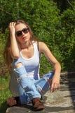 Menina 'sexy' bonita com cabelo longo em um t-shirt branco e nas calças de brim que sentam-se nas madeiras em um dia ensolarado Fotografia de Stock Royalty Free