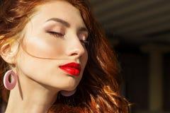 Menina 'sexy' bonita com cabelo vermelho com os bordos vermelhos grandes com composição na cidade em um dia de verão ensolarado Foto de Stock