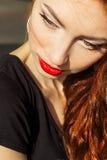 Menina 'sexy' bonita com cabelo vermelho com os bordos vermelhos grandes com composição na cidade em um dia de verão ensolarado Fotos de Stock Royalty Free