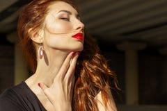 Menina 'sexy' bonita com cabelo vermelho com os bordos vermelhos grandes com composição na cidade em um dia de verão ensolarado Fotografia de Stock