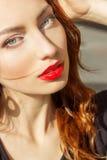 Menina 'sexy' bonita com cabelo vermelho com os bordos vermelhos grandes com composição na cidade em um dia de verão ensolarado Foto de Stock Royalty Free