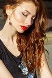 Menina 'sexy' bonita com cabelo vermelho com os bordos vermelhos grandes com composição na cidade em um dia de verão ensolarado Imagem de Stock
