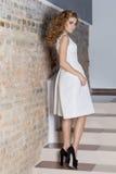 A menina 'sexy' bonita elegante com penteado bonito e a noite brilhante preparam no vestido branco da noite e nas sapatas pretas, Imagens de Stock