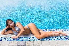 A menina 'sexy' bonita encontra-se na borda do banho de sol da piscina Vocação do verão foto de stock royalty free