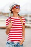 Menina 'sexy' bonita no short e t-shirt listrado, nos óculos de sol, no chapéu, fora Mulher bronzeada no verão imagem de stock royalty free