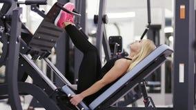 A menina 'sexy' bonita no sportswear preto que faz exersices no mashine da imprensa do pé ajustou-se no gym Heathcare e bem estar filme