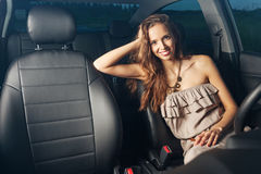 Menina 'sexy' bonita que senta-se atrás da roda de um carro e que sorri fora Foto de Stock Royalty Free