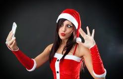 A menina 'sexy' bonita que veste Papai Noel veste-se com smartphone Fotografia de Stock Royalty Free