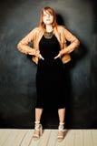 Menina 'sexy' Cabelo vermelho Vestido preto Revestimento de couro imagens de stock
