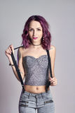 Menina 'sexy' com cabelo roxo e uma tatuagem no corpo que levanta no fundo cinzento Mulher perfeita em calças de brim cinzentas e foto de stock