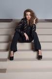 A menina 'sexy' com os bordos vermelhos sedutores e brilhantes bonitos compõem nas calças pretas e em uma camisa preta, fotografi Imagem de Stock