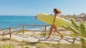 Menina 'sexy' com pele bronzeada que anda ao longo da praia com prancha Jovem mulher bonita no roupa de banho do biquini Conceito filme