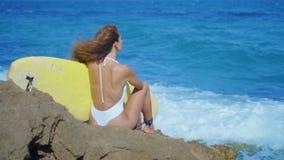 Menina 'sexy' com pele bronzeada que anda ao longo da praia com prancha Jovem mulher bonita no roupa de banho do biquini Conceito video estoque