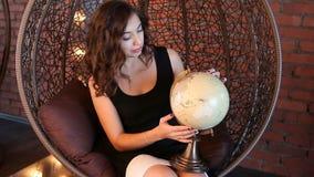 Menina 'sexy' com um globo na poltrona vídeos de arquivo