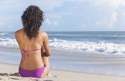 Menina 'sexy' da mulher que senta-se no biquini na praia foto de stock