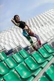 Menina 'sexy' do esporte que levanta no estádio A menina da aptidão com esportes figura nas caneleiras e na parte superior preta  imagem de stock royalty free