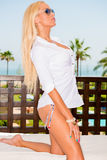 Menina 'sexy' elegante Kneeing na cama de Sun Imagem de Stock Royalty Free