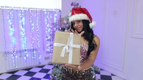 Menina 'sexy' em um chapéu de Santa com um presente em suas mãos video estoque