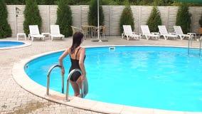A menina 'sexy' em um roupa de banho preto entra na associação em etapas vídeos de arquivo
