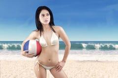 A menina 'sexy' guarda uma bola na praia Fotos de Stock Royalty Free