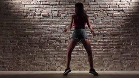 A menina 'sexy' no short da parte superior e da sarja de Nimes da colheita dança o twerk contra uma parede de tijolo Movimento le filme