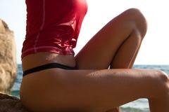 A menina 'sexy' no sportswear e o tanga amarram o assento no penhasco de Fotografia de Stock Royalty Free