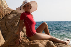 Menina 'sexy' no sportwear e tanga na praia rochosa Foto de Stock