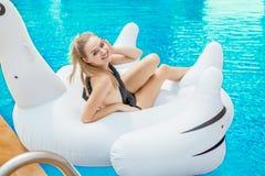 Menina 'sexy' no terno de natação preto que encontra-se nos mattres infláveis fotos de stock