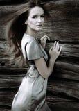Menina 'sexy' no vestido de seda verde em um fundo de uma parede de madeira Imagens de Stock Royalty Free