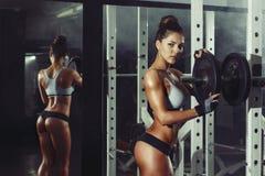 A menina 'sexy' nova atlética ajusta o peso no barbell no gym foto de stock royalty free